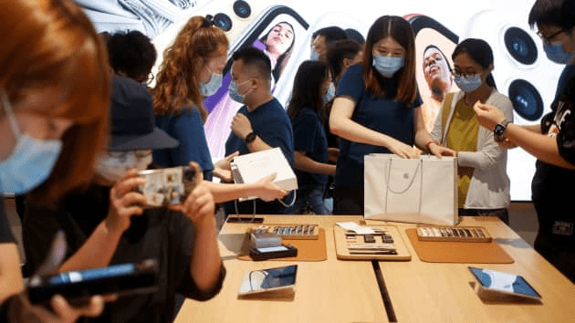 People purchase Apple products in the new Apple flagship store on its opening day following an outbreak of the coronavirus disease (COVID-19) in Sanlitun in Beijing, China, July 17, 2020.