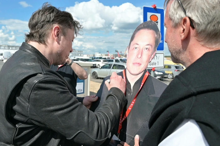 Elon Musk, left, signs a cardboard cut-out of himself during a visit to a Tesla factory under construction in Germany