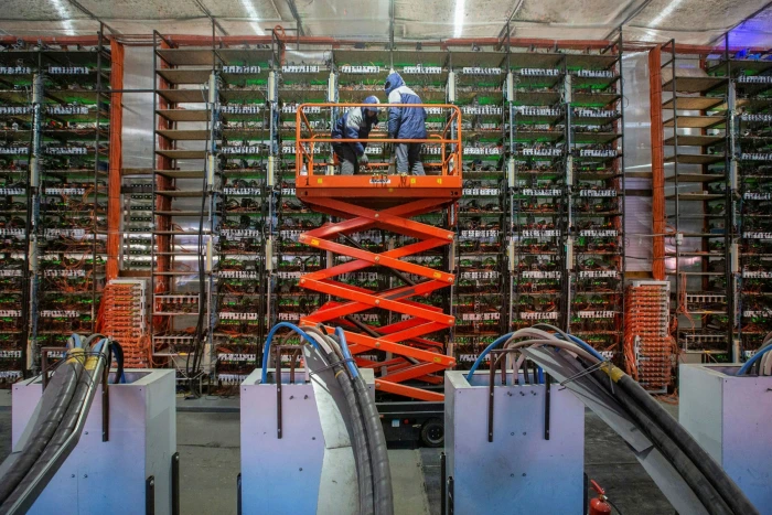 Engineers install mining rigs at a cryptocurrency mining farm in Russia